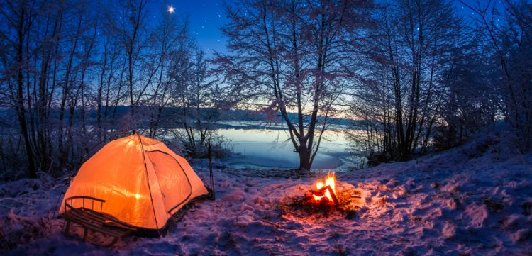 Camping by a lake with a tent and camp fire.