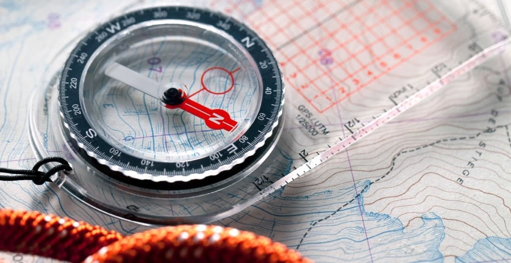 Compass and climbing rope on a topography map.