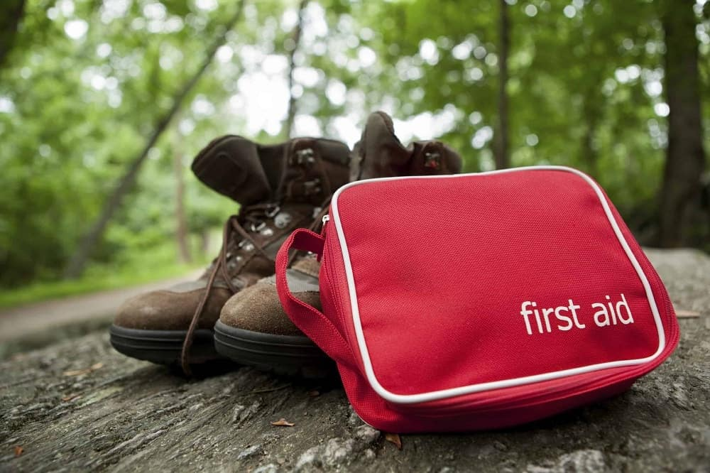 First aid kit sitting against a pair of hiking boots outside.