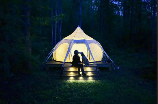 A woman and her dog enjoying the tent with lights on a wooden platform.