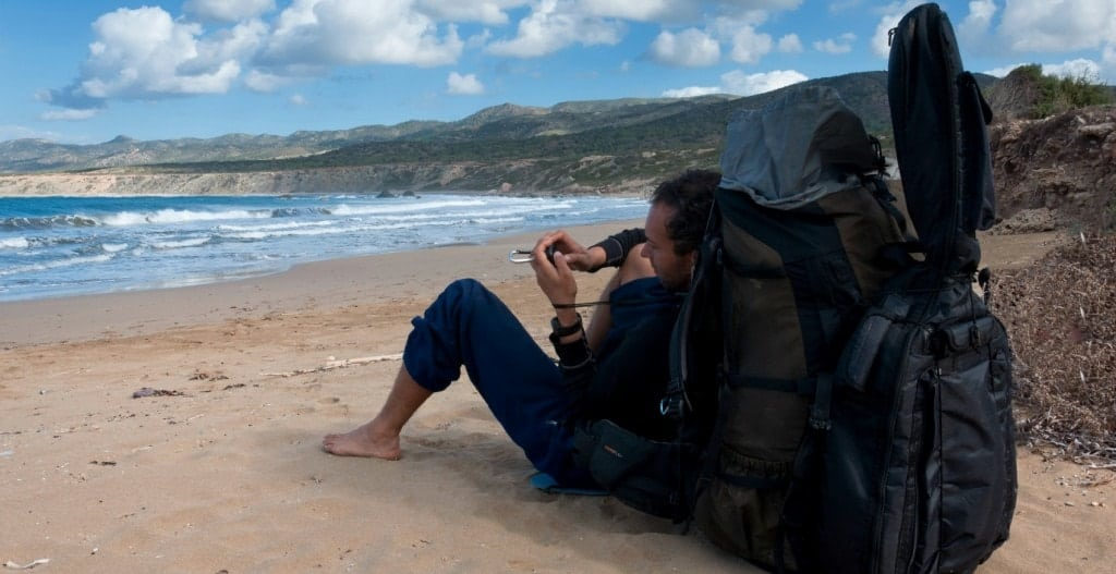 A hiker sitting with an oversized backpack and guitar on the beach.