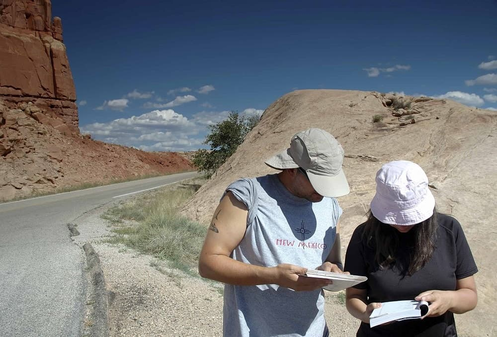 A couple looking at a guide book during a hike.
