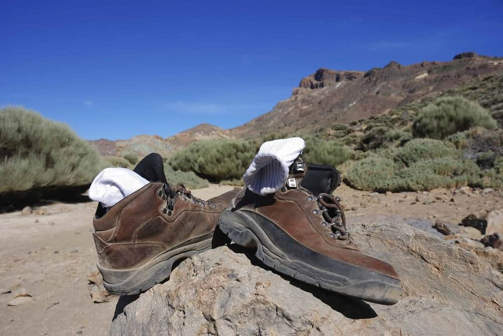 A pair of hiking boots with sock liners in the mountains.