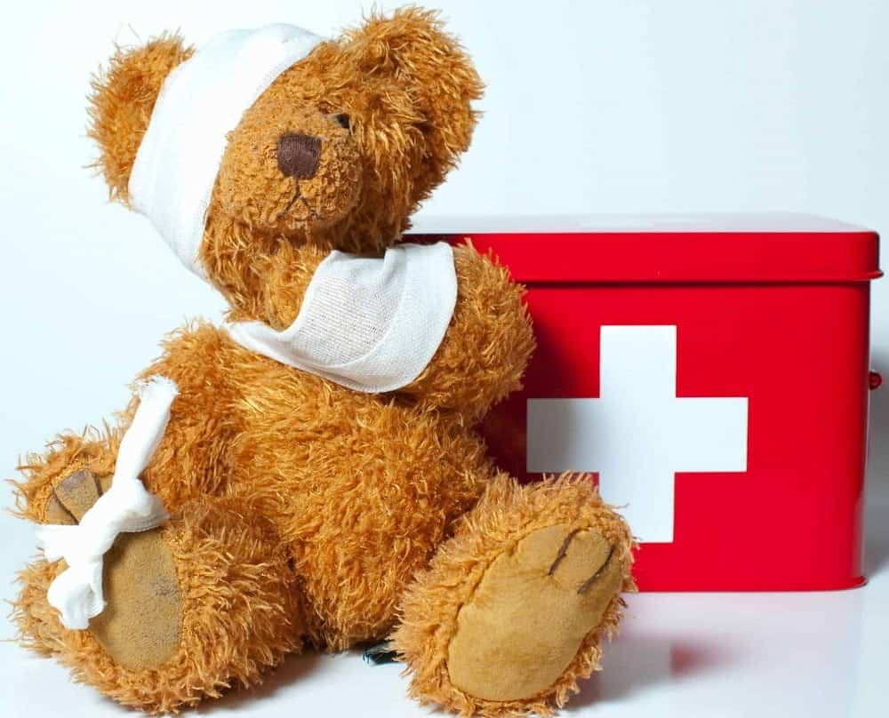 Teddy bear with bandages and first aid kit.