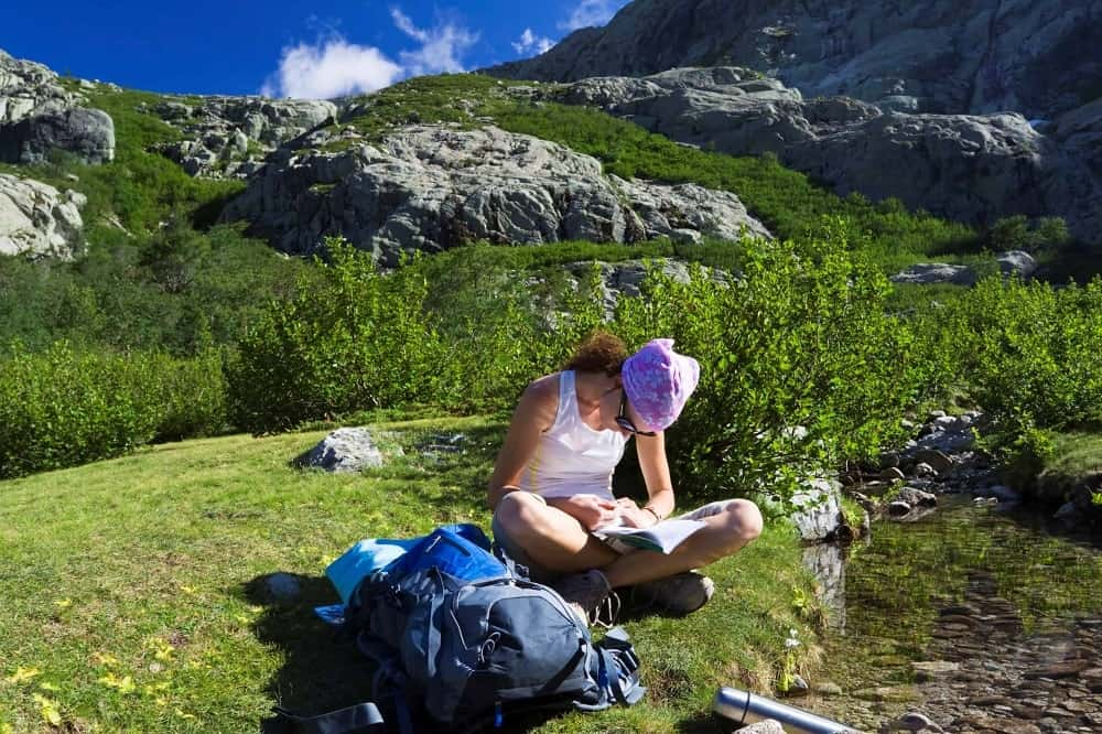 A hiker reading a book in the mountains.