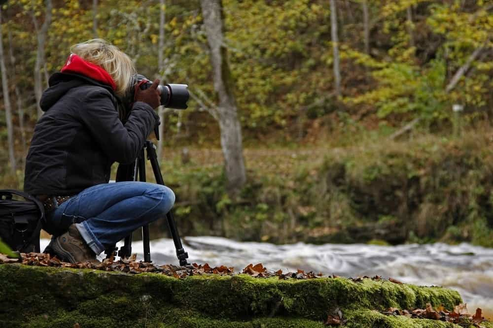 A hiker taking pictures outdoors next to a stream.