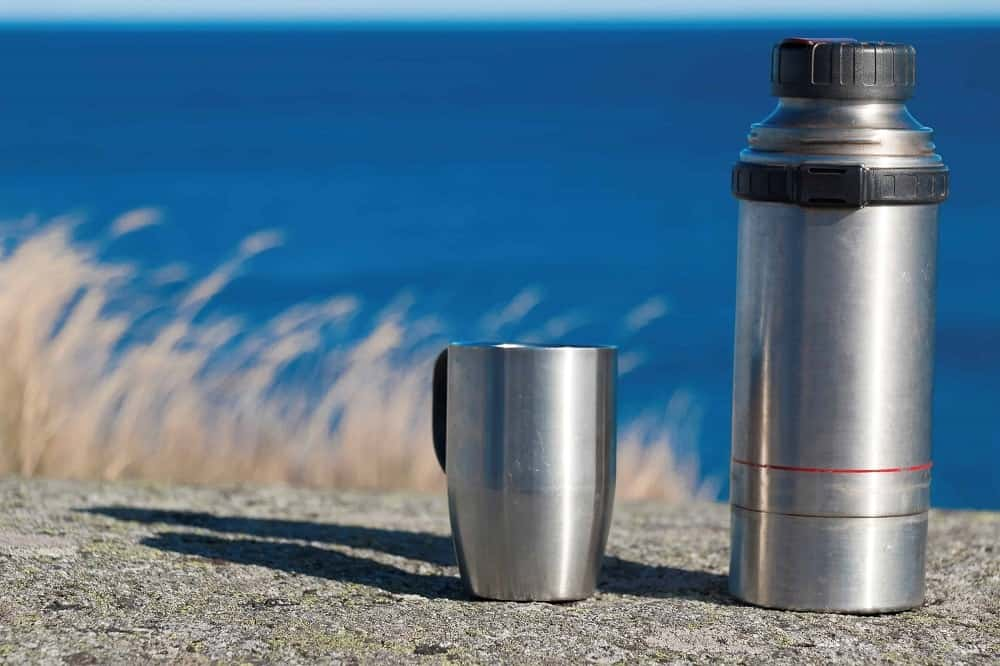 Stainless steel thermos and coffee mug sitting on a rock ledge.