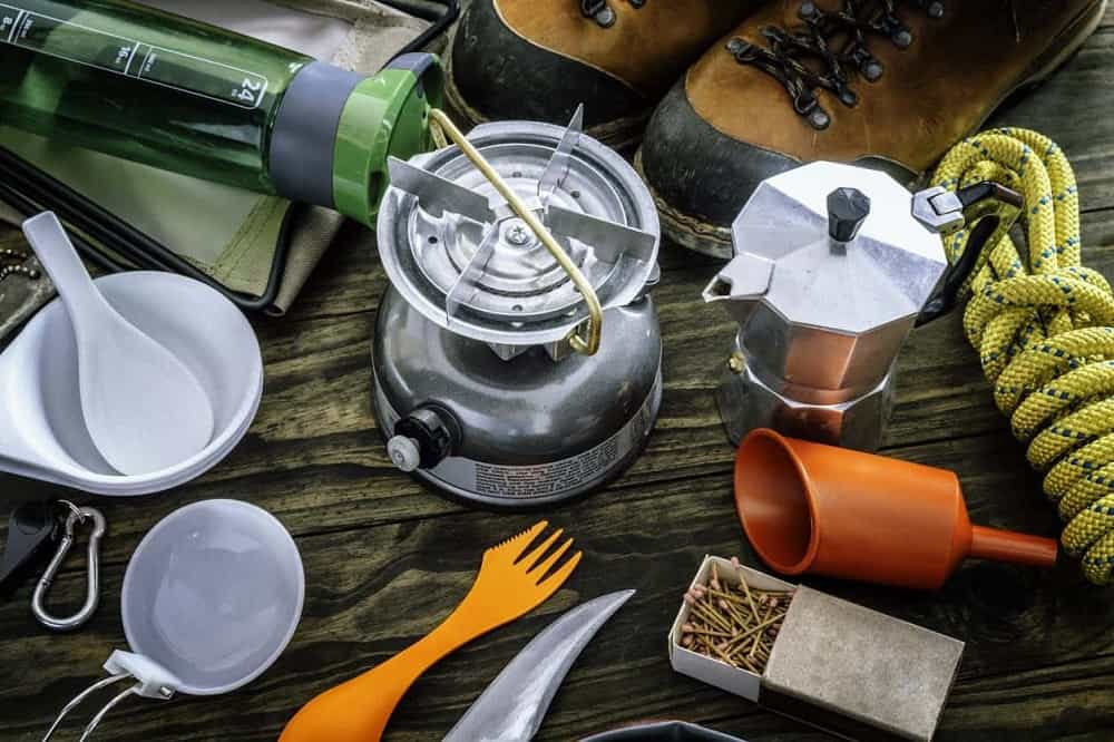 Various camping gears and equipment on a wooden table.