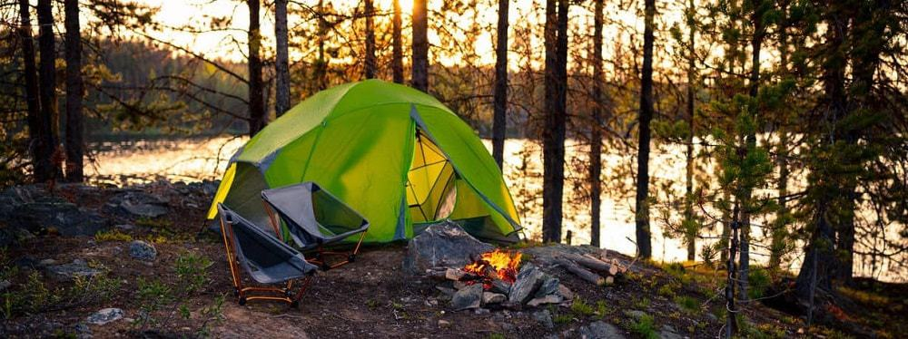 A camping scenery of a tent, camping chairs and campfire overlooking a lake.