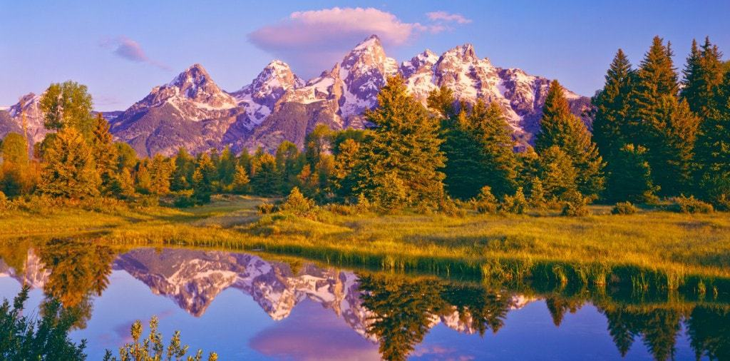 A view of the Grand Tetons with reflection on the water.