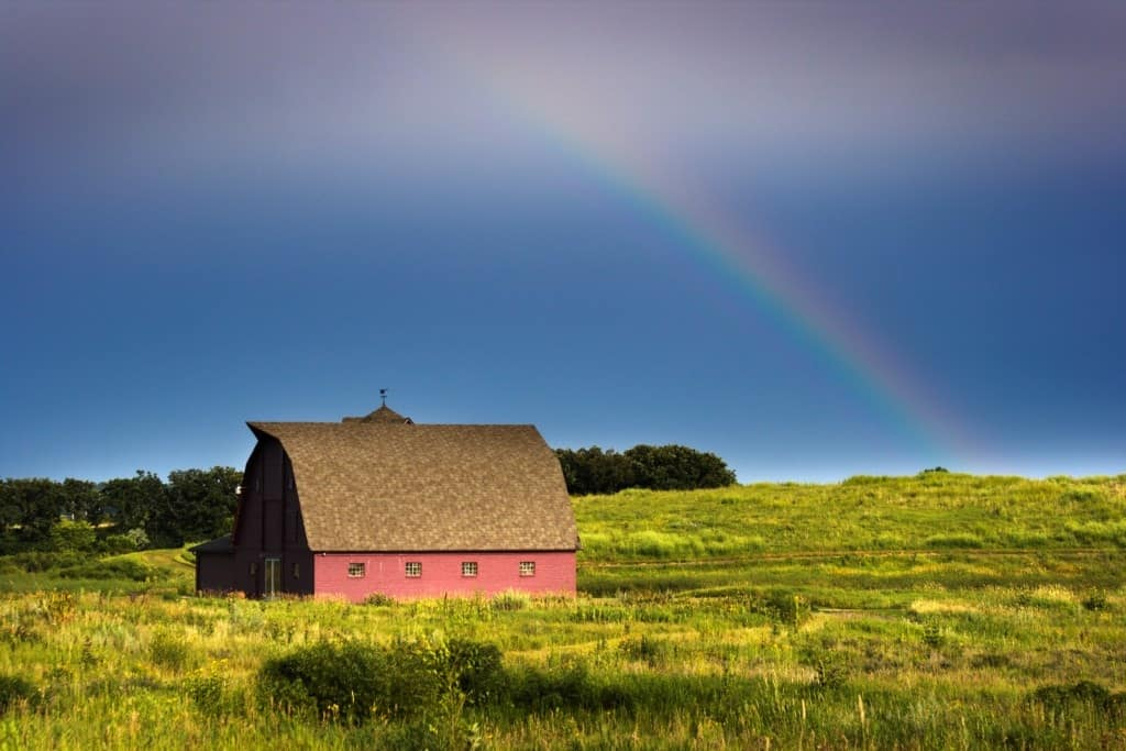 A Midwest prairie landscape with barn and rainbow.