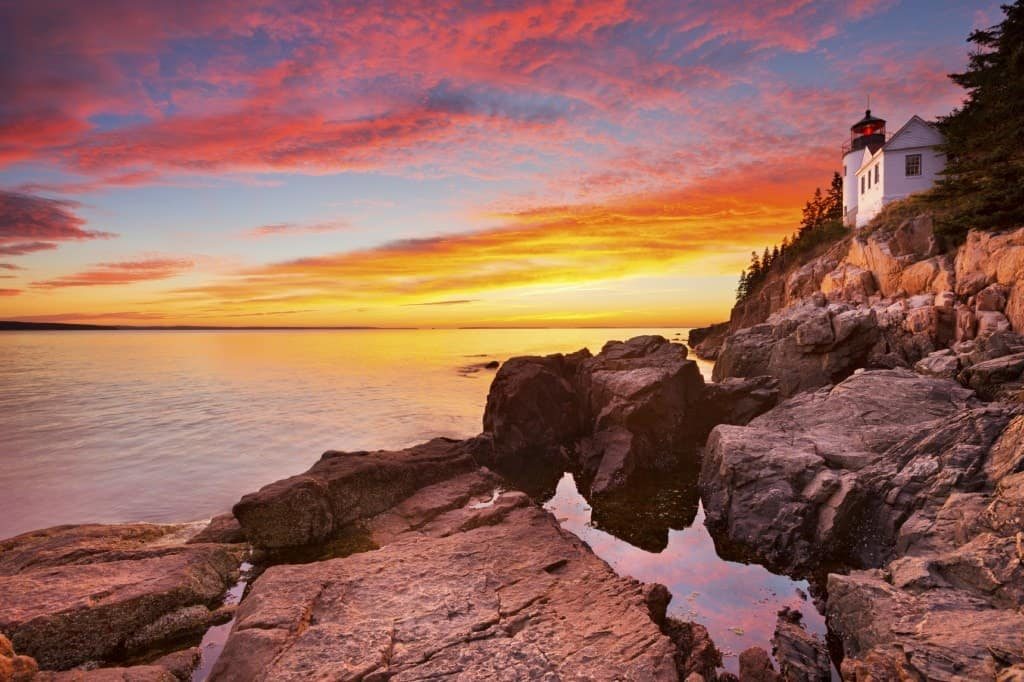 A picturesque view of Acadia National Park sunset with a lighthouse.