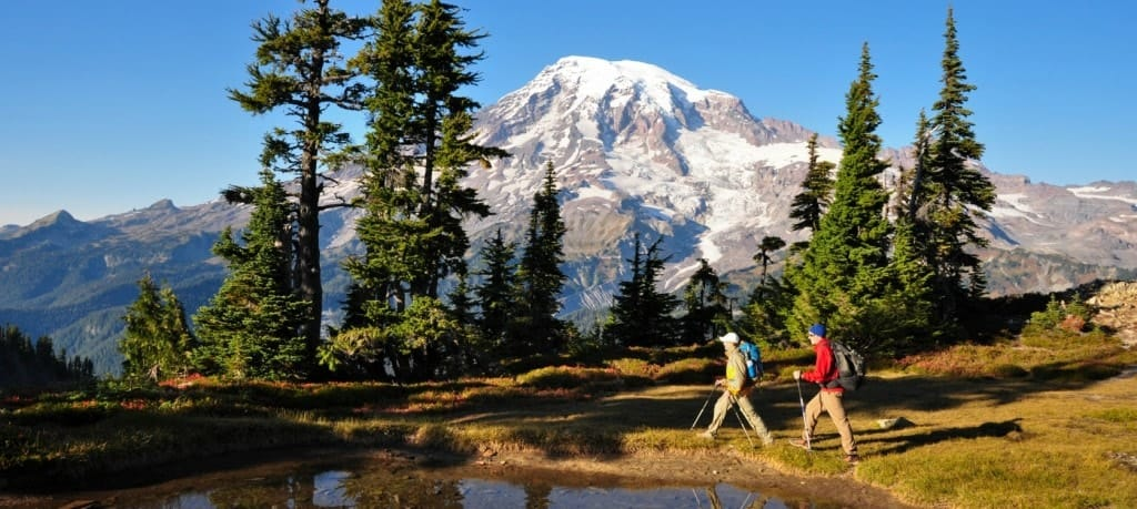 A look at hikers hiking by the water with Mt Rainier in the background.