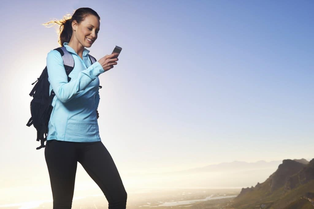 A woman sending her itinerary on her phone while hiking.