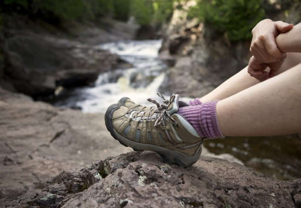 A hiker wearing boots sitting by a river.