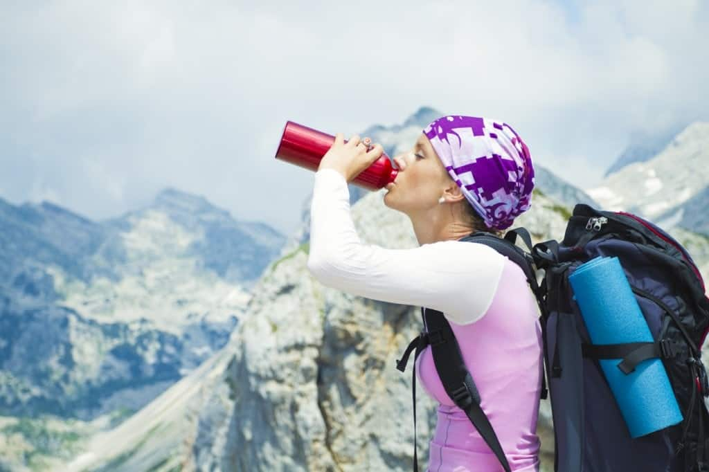 A hiker drinking water in the mountains.