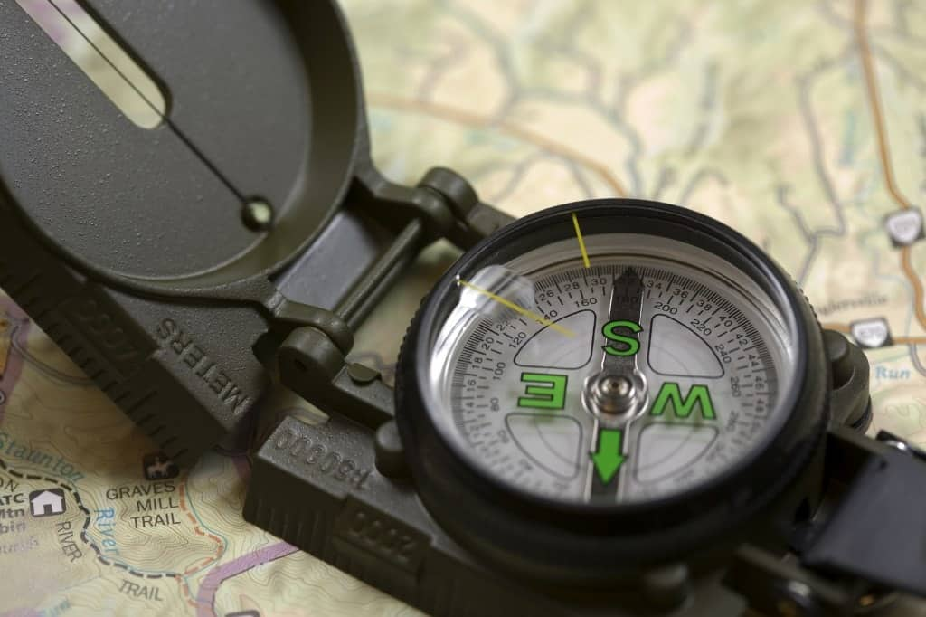 A close look at a hiker's compass sitting on a map.