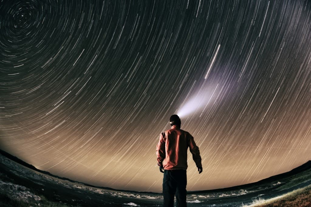 A hiker star gazing while wearing a headlamp.