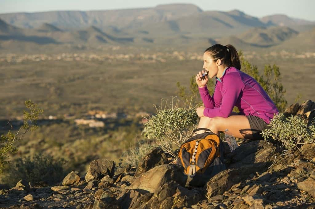 A woman taking a break from her hike and having a snack.