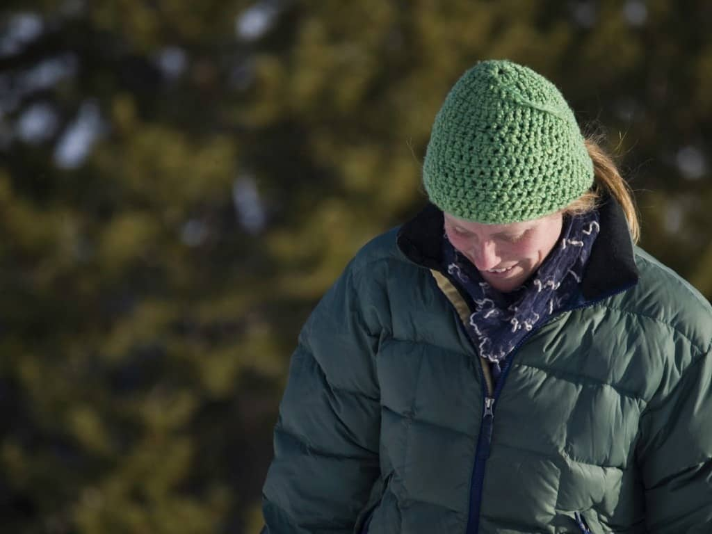 A Hiker wearing a puffy jacket with a hat to stay warm.