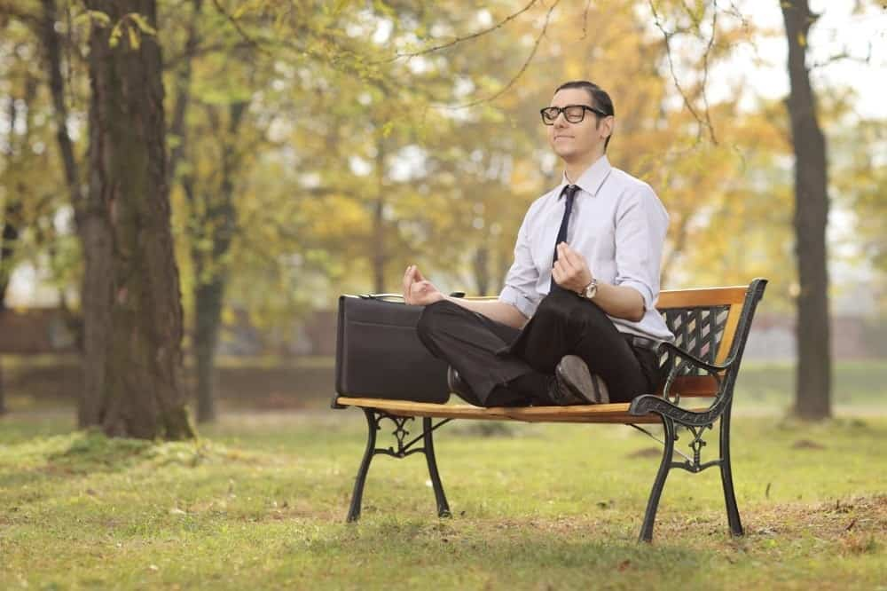A businessman meditating while seated on a bench in a park.