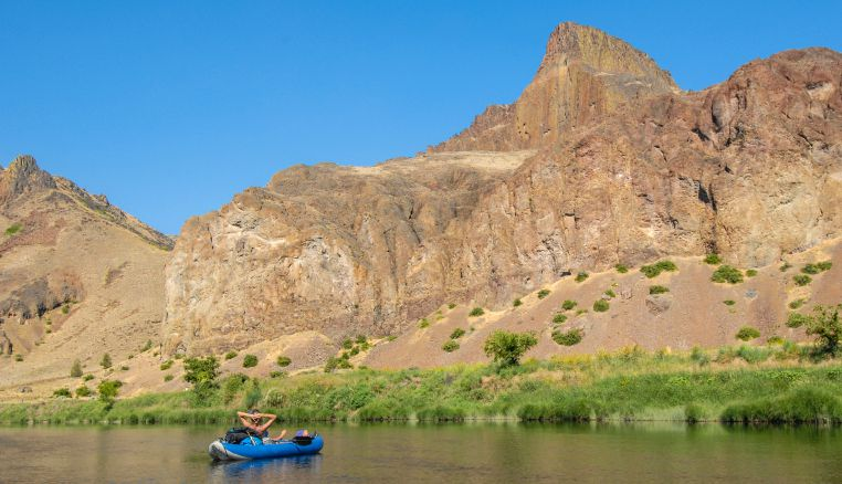 Rafter in an IK relaxing on the NF John Day river.