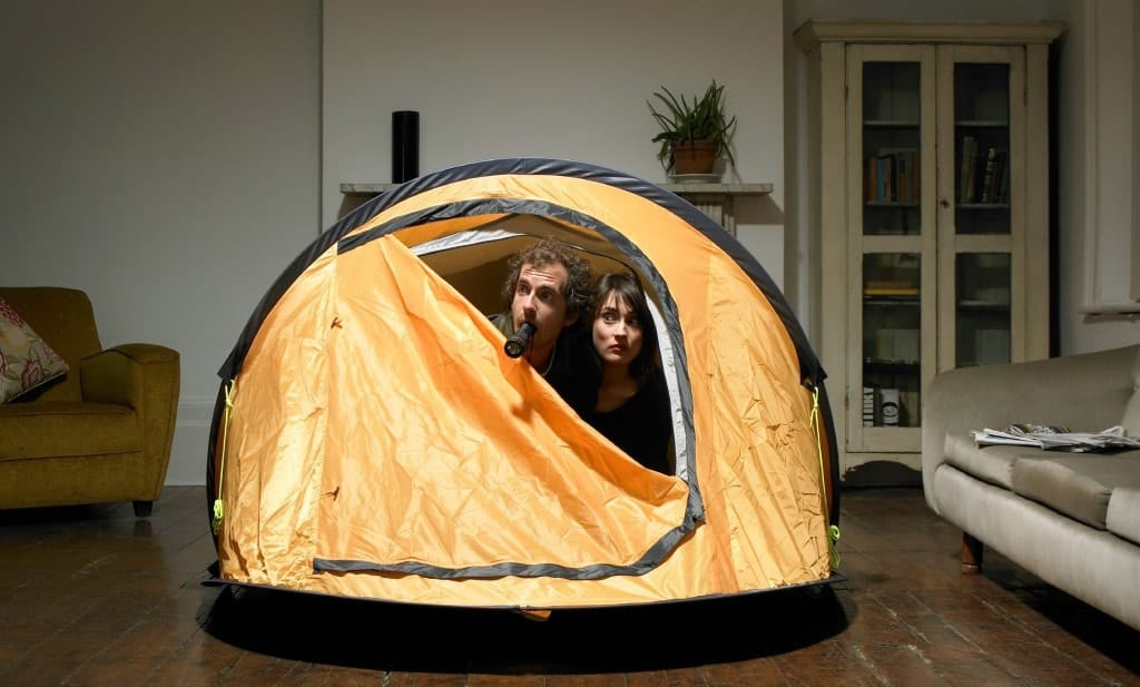 A couple camping in a tent that is set up in the living room.