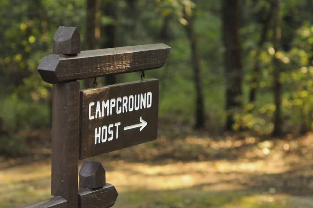 A wooden camp host sign hanging in a campground.