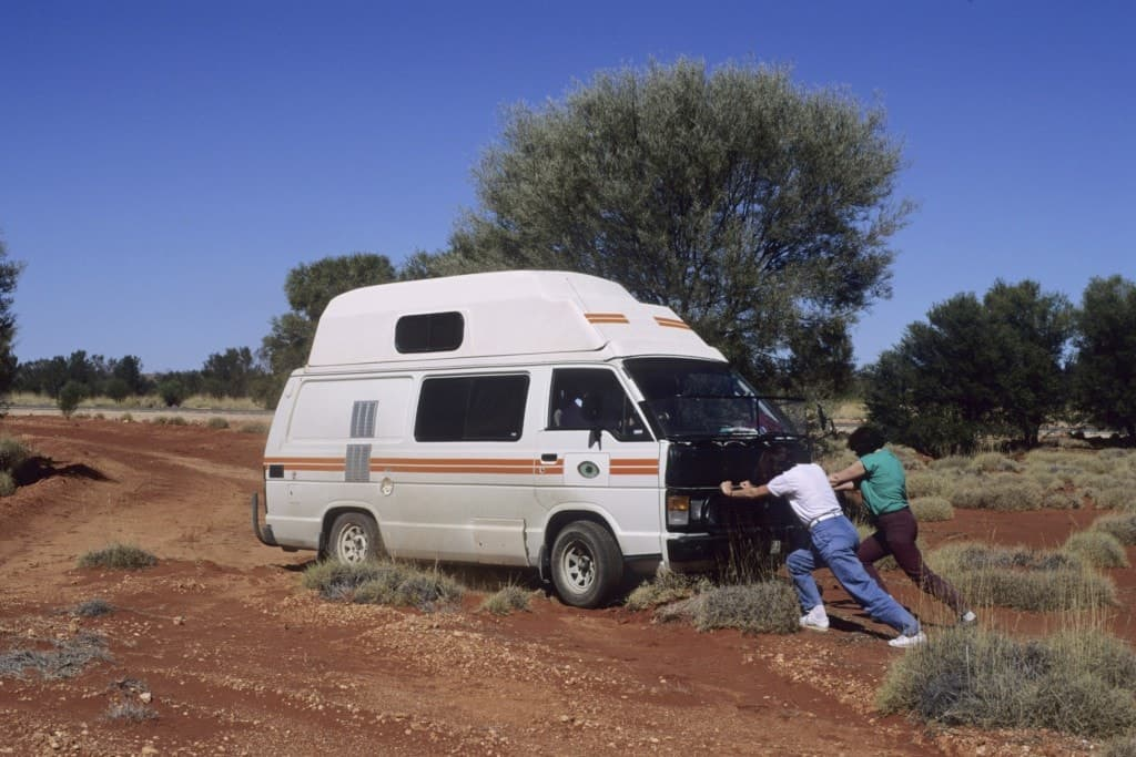 Two people pushing a camper van out of the dirt road.