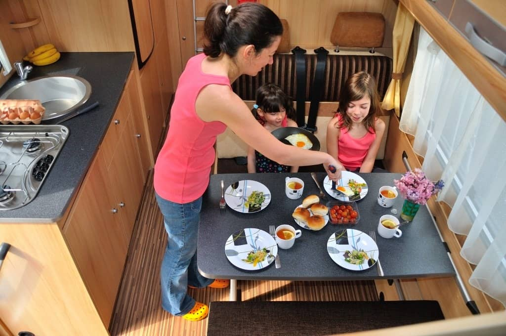 A family eating a camp style meal in a camper kitchen.
