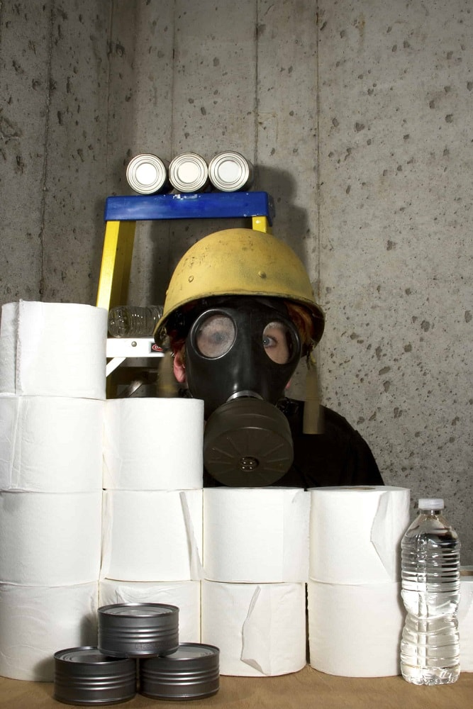 A person wearing a gas mask with survival items such as toliet paper, water and canned goods.