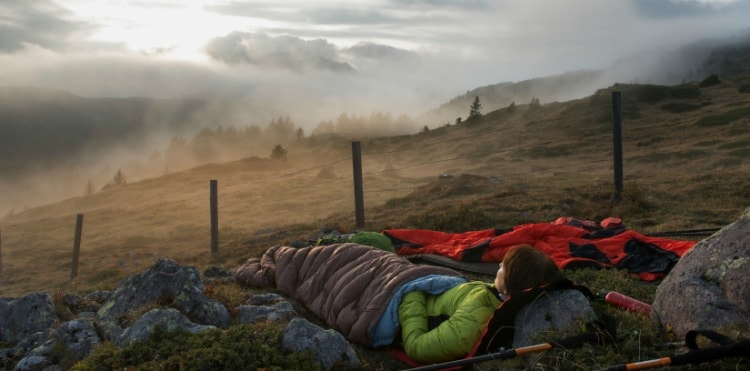 Outdoors person cozy in a sleeping bag looking at the outside scenery.