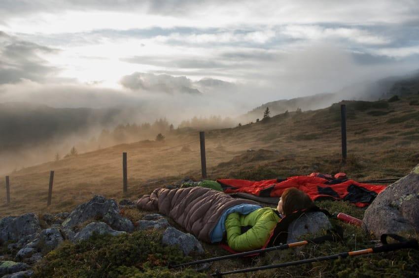 Camper sleeping outdoors against some rocks.
