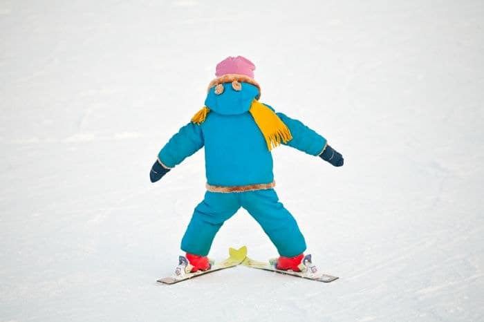 A little child doing his first downhill on alpine skis, standing back closeup on snow background.