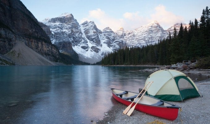 Family tent and canoe on a glacial lake in the Canadian Rockies.