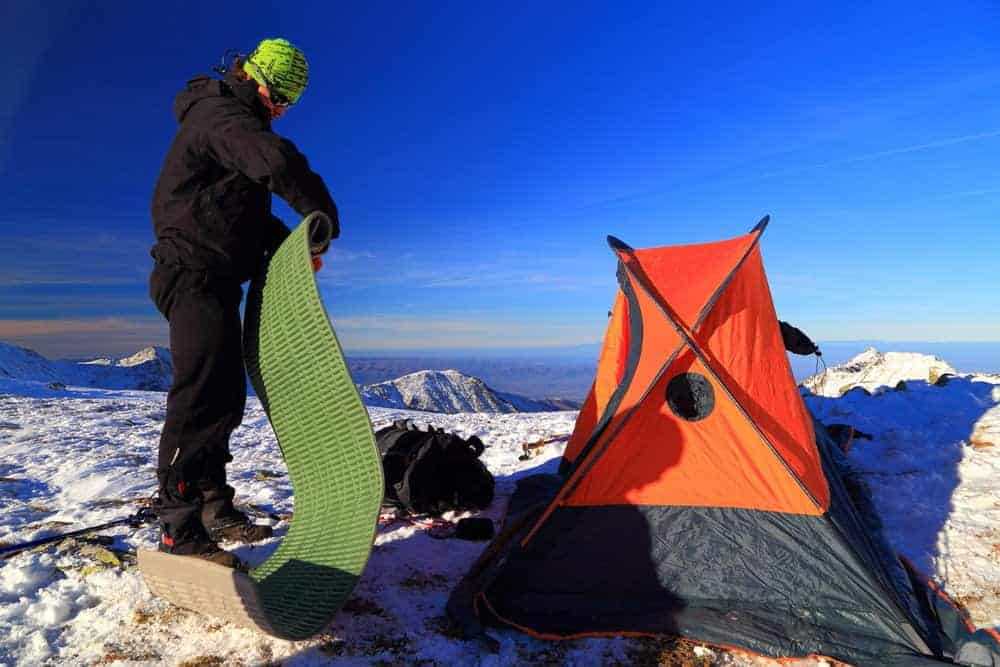 Man camping on mountain rolling up sleeping pad.