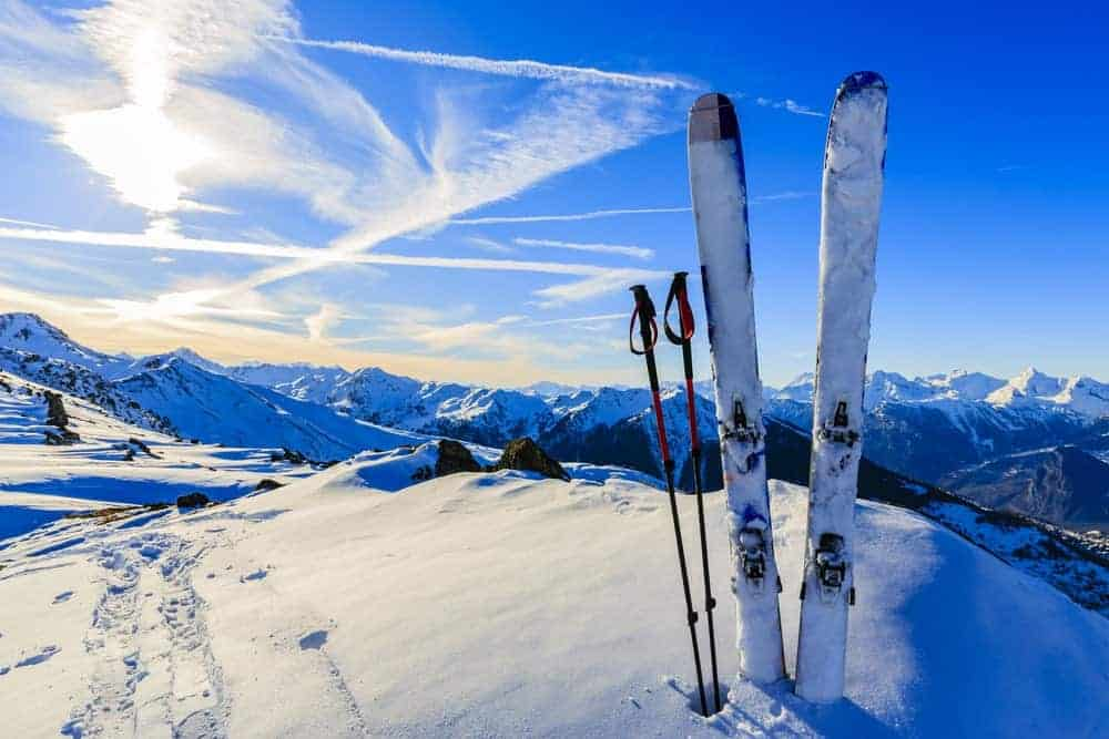 A set of skis sticking on the snow peak of a mountain.