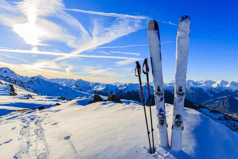 A set of skis sticking on the snow peak of a mountain.