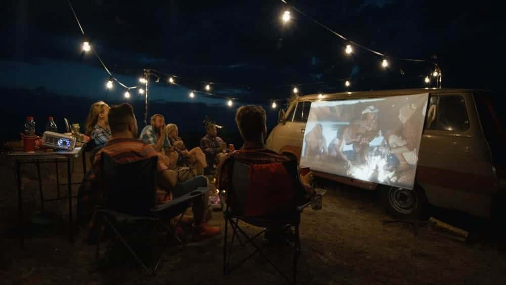 Friends watching a movie on a projector screen against a campervan.