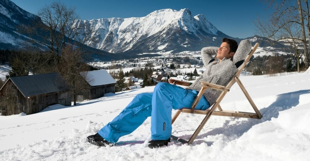 A person relaxing in the sun with mountains behind.
