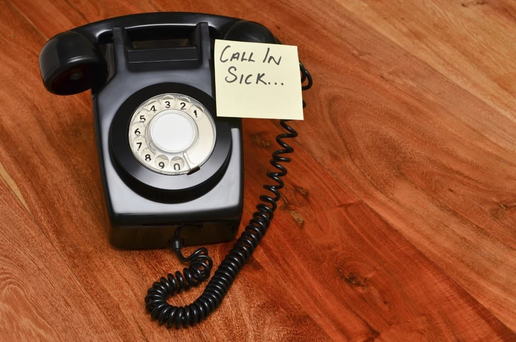 A rotary telephone with a post it reminding you to call in sick.