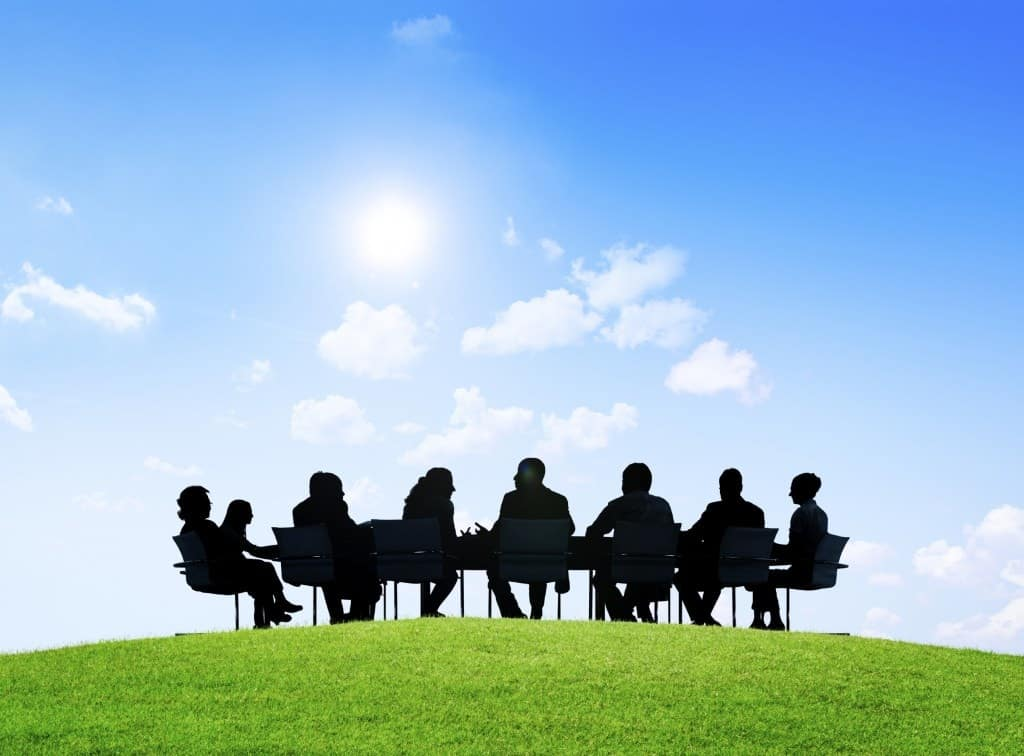 People sitting around a meeting table in the outdoors and under the sunshine.