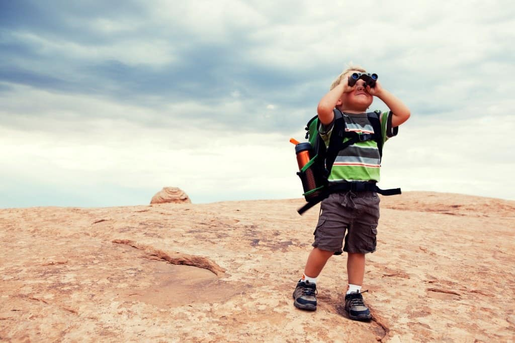 A kid looking through binoculars outside in the mountains.