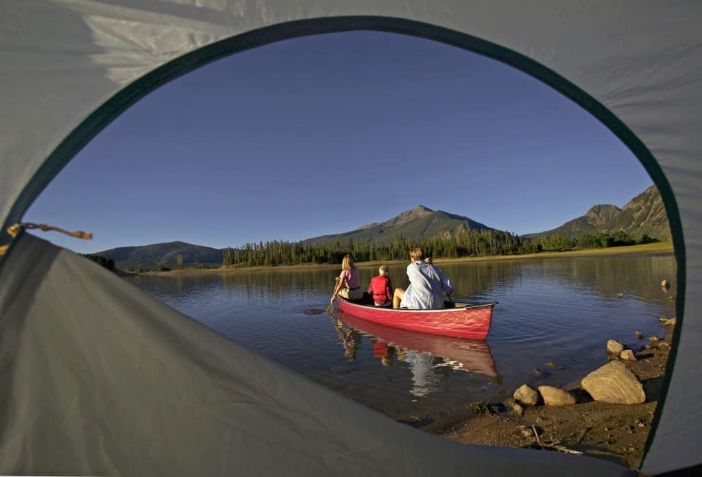 A family canoeing with beautiful weather as seen through a tent.