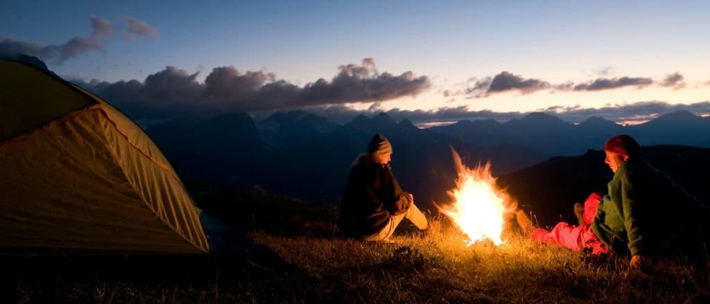 A couple by their tent camping in the wilderness with campfire.