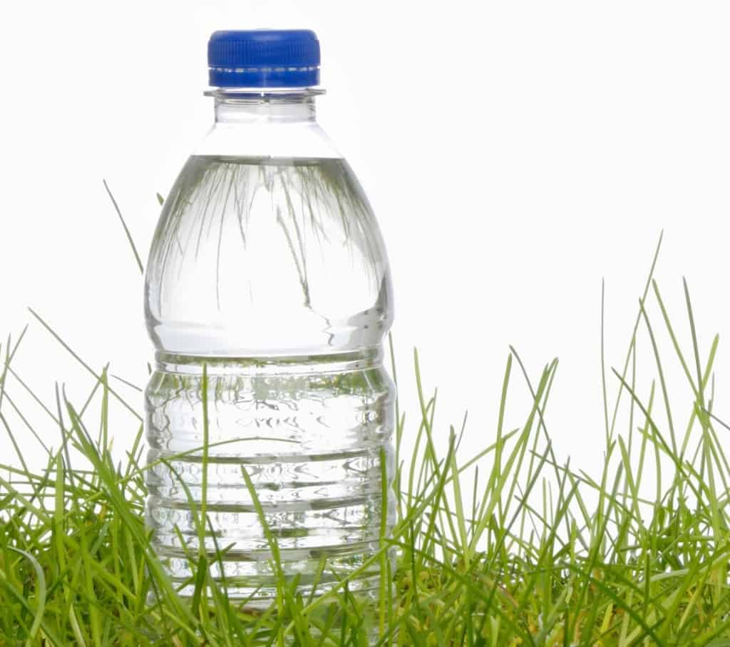 A close look at a water bottle on grass.