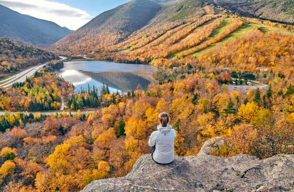 Woman sitting on top of a mountain overlooking Echo Lake in New Hampshire.