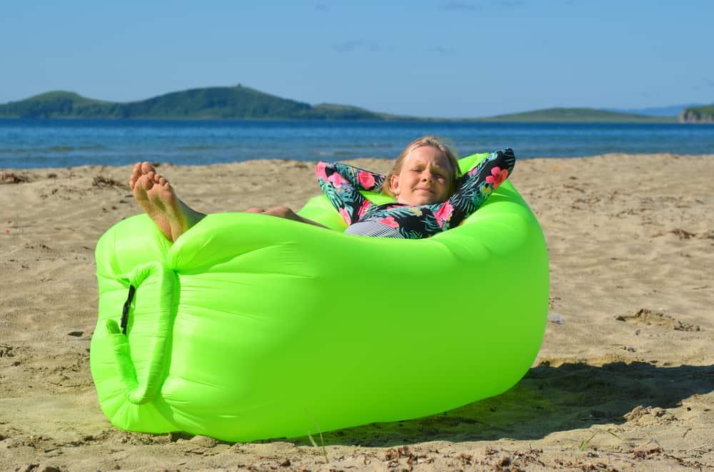 A girl resting on a green air lounger near the beach.