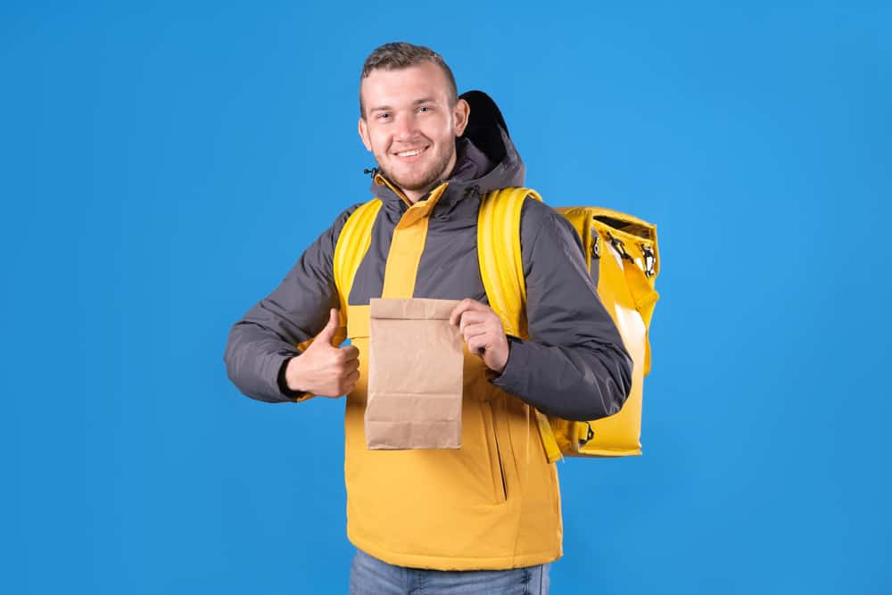 Man with a backpack cooler holding a paper bag.