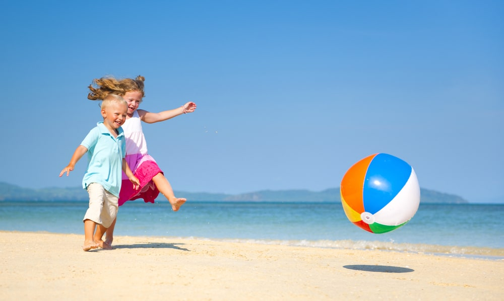 Kids playing beach ball by the seashore.
